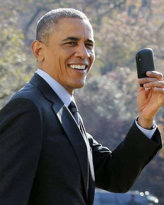 US President Barack Obama shows his Blackberry as he walks on the South Lawn of the White House in Washington, DC. Obama forgot to take his Blackberry devise and returned to pick it up at The White House before his departure to Las Vegas, Nevada on November 21, 2014.