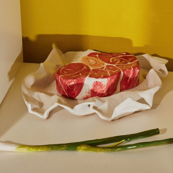 Ceramic sculptures of a raw steak in butcher paper and a green onion