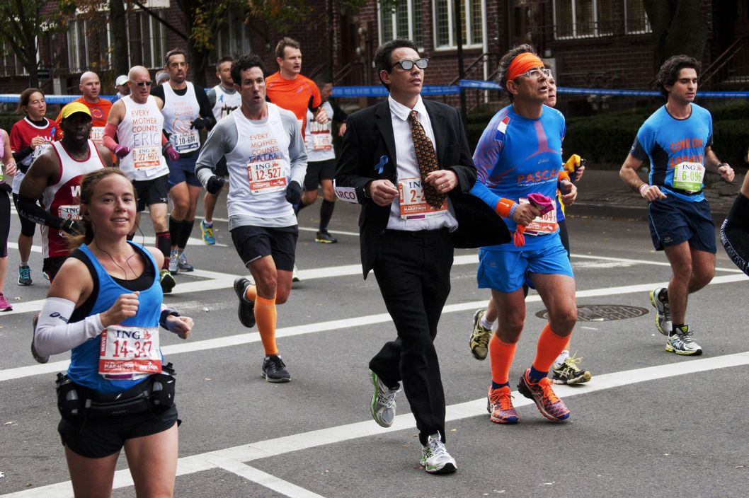 A man wearing a business suit is one of the than 50,000 runners who competed in the New York City Marathon on Sunday, 3 November, 2013. -- More than 50,000 runners competed in the New York City Marathon on Sunday, 3 November, 2013. Kenya's Priscah Jeptoo won the women's race with a time of 2 hours, 25 minutes, 7 seconds. Kenya's Geoffrey Mutai, 32, won the men's race in 2:08:24.
