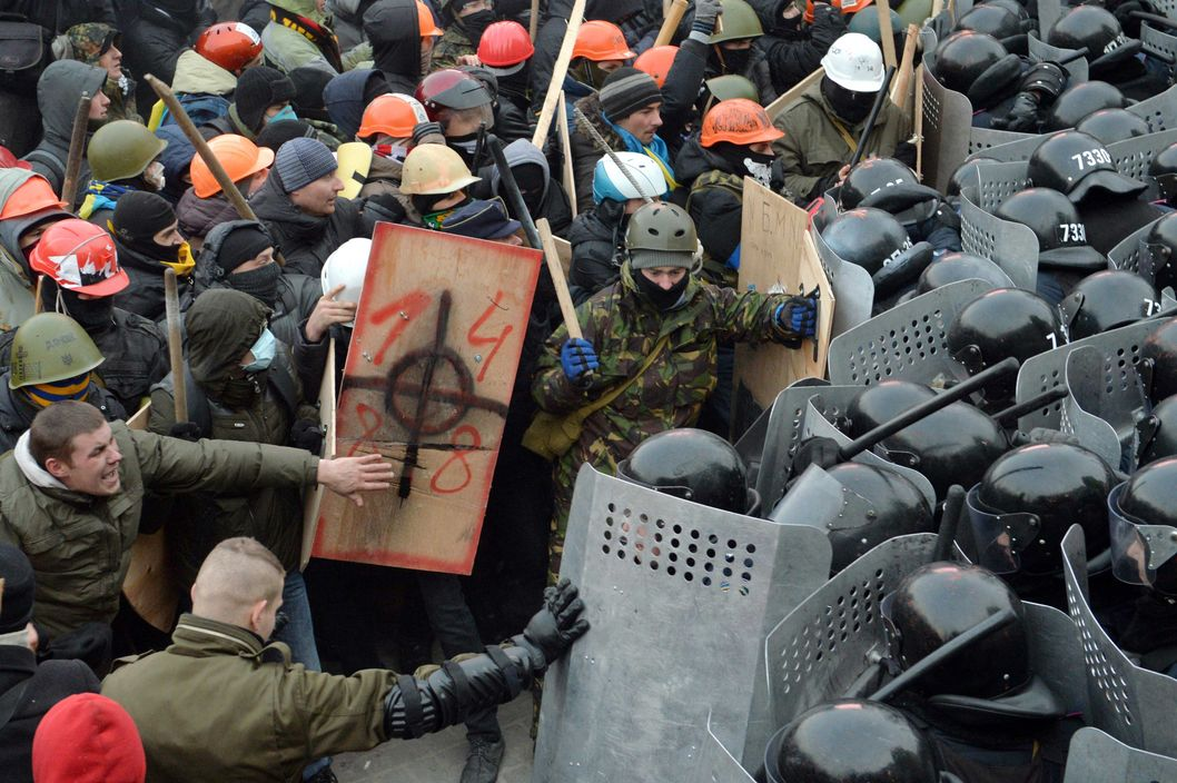 Protesters clash with riot police on January 19, 2014 during an opposition rally in the centre of the Ukrainian capital Kiev in a show of defiance against strict new curbs on protests. 200,000 protesters expressed frustration over the lack of a clear programme from the opposition leaders after almost two months of protests over the government's ditching of a pact with the EU under Russian pressure. Ukrainian police used tear gas, stun grenades and water cannon in a bid to disperse the hundreds of people who sought to storm police cordons near the Verkhovna Rada parliament in the capital. AFP PHOTO / SERGEI SUPINSKY        (Photo credit should read SERGEI SUPINSKY/AFP/Getty Images)