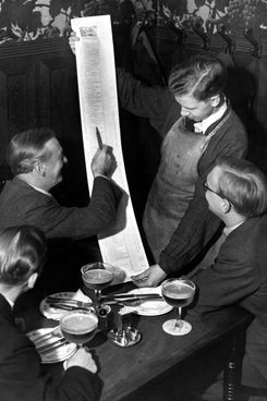 Too long to place on the table, the waiters at Oesar Davidson's famous restaurant in Copenhagen have to hold the menus for their customers, 1938.