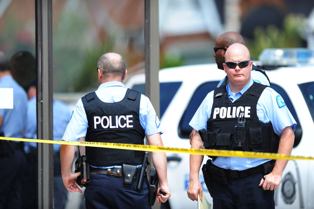 "Police officers are seen at a crime scene involving a shooting of a man by St. Louis Metropolitan Police on August 19, 2014.  Police in the US city of St. Louis shot dead another suspect on Tuesday, a short distance from a suburb that is the scene of protests over the killing of an unarmed black teenager.  St. Louis Police Chief Sam Dotson said in a tweet that officers had responded to a call and found an apparently agitated man, armed with a knife who yelled ""kill me now"" and approached the patrol.     AFP PHOTO / Michael B. THOMAS        (Photo credit should read Michael B. Thomas/AFP/Getty Images)"