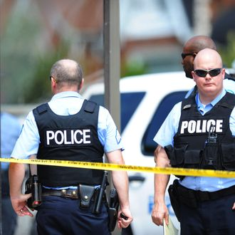 Police officers are seen at a crime scene involving a shooting of a man by St. Louis Metropolitan Police on August 19, 2014. Police in the US city of St. Louis shot dead another suspect on Tuesday, a short distance from a suburb that is the scene of protests over the killing of an unarmed black teenager. St. Louis Police Chief Sam Dotson said in a tweet that officers had responded to a call and found an apparently agitated man, armed with a knife who yelled