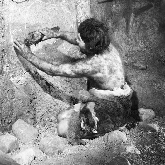 CAVEMAN CARVING ON CAVE WALL