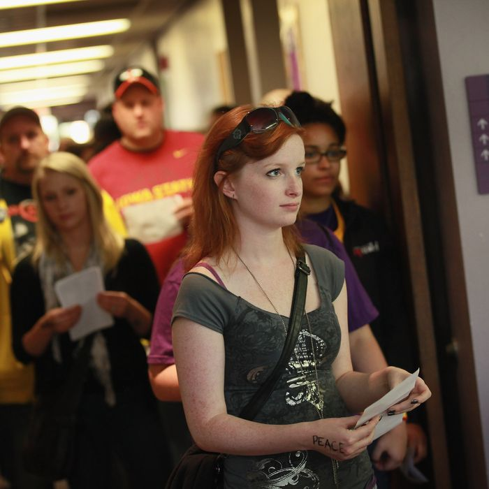 CEDAR FALLS, IA - SEPTEMBER 28: Students wait in line to vote on the campus of the University of Northern Iowa (UNI) on September 28, 2012 in Cedar Falls, Iowa. Most of the voters in the line walked from a nearby rally with first lady Michelle Obama to the polling place to cast their votes. Yesterday Iowa began early voting in select locations throughout the state. (Photo by Scott Olson/Getty Images)