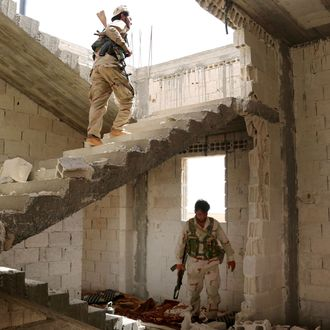 Fighters from Syria's Manbij military council are seen on June 15, 2016 in a building on the outskirts of the northern Syrian town of Manbij, which is held by jihadists of the Islamic State (IS) group, during an operation to try to retake the town.