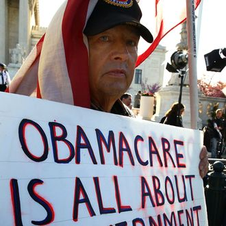 WASHINGTON, DC - MARCH 26: Ron Kirby holds a sign while marching in protest of the Patient Protection and Affordable Care Act in front of the U.S. Supreme Court on March 26, 2012 in Washington, DC. Today the high court, which has set aside six hours over three days, will hear arguments over the constitutionality President Barack Obama's Patient Protection and Affordable Care Act. (Photo by Mark Wilson/Getty Images)