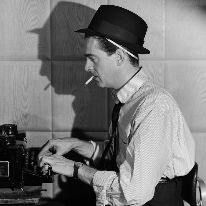 Newspaper reporter at typewriter smoking a cigarette. Undated photograph. --- Image by ? Bettmann/CORBIS