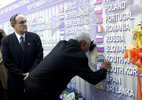 New York City Mayor Rudolph Giuliani watches former South African President Nelson Mandela sign the Wall of Nations, which represents the countries that lost individuals during the September 11th terrorist attacks on the World Trade Center site, during a tour of ground zero.