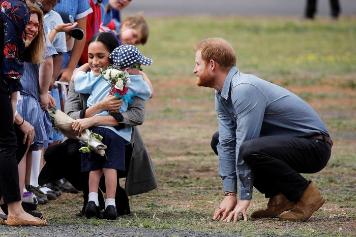 Meghan Markle hugs a child in Dubbo as Prince Harry looks on.