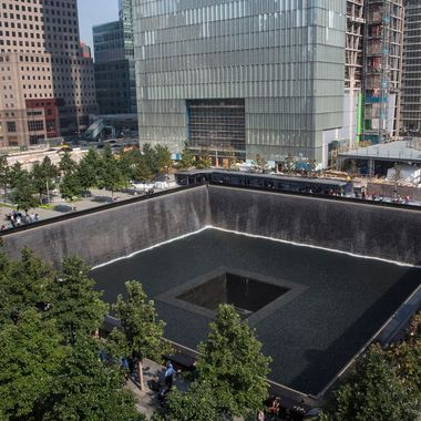 People gather around the NorthTower pool during memorial ceremonies for the twelfth anniversary of the terrorist attacks on lower Manhattan at the World Trade Center site on September 11, 2013 in New York City.