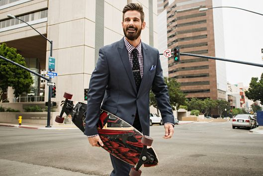 Young businessman carrying skateboard and crossing street
