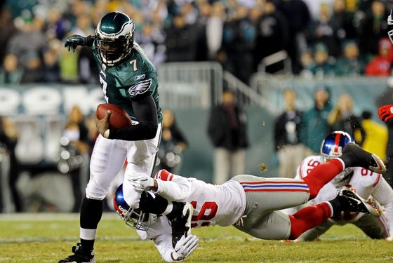 Michael Vick #7 of the Philadelphia Eagles runs with the ball against Antrel Rolle #26 of the New York Giants at Lincoln Financial Field on November 21, 2010 in Philadelphia, Pennsylvania.