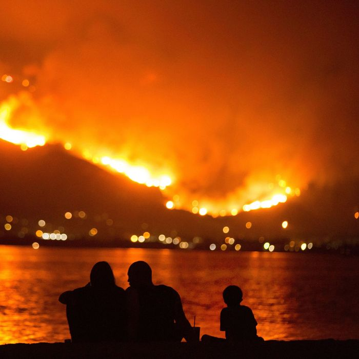 A family sits along the shore of Lake Elsinore as they watch the Holy Fire burn in the distance, in Lake Elsinore, Calif. More than a thousand firefighters battled to keep a raging Southern California forest fire from reaching foothill neighborhoods.
