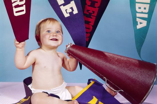 17 Jun 1965 --- 1960s smiling happy baby with college pennants holding cheerleader megaphone --- Image by ? ClassicStock/Corbis