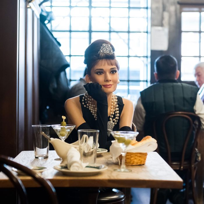 A wax sculpture of Audrey Hepburn in the Breakfast at Tiffany's dress sitting at Peter Luger, a steakhouse in Brooklyn.