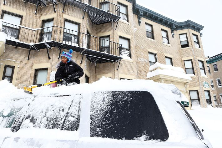 BOSTON, MA - FEBRUARY 9:  Saniyyah Phillips, 8, scrapes the snow off of the top of her father's car on February 9, 2013 in the Brighton neighborhood of Boston, Massachusetts. The powerful storm has knocked out power to 650,000 and dumped more than two feet of snow in parts of New England. (Photo by Jared Wickerham/Getty Images)