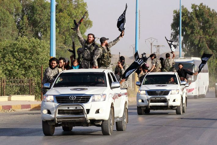 Militant Islamist fighters wave flags as they take part in a military parade along the streets of Raqqa