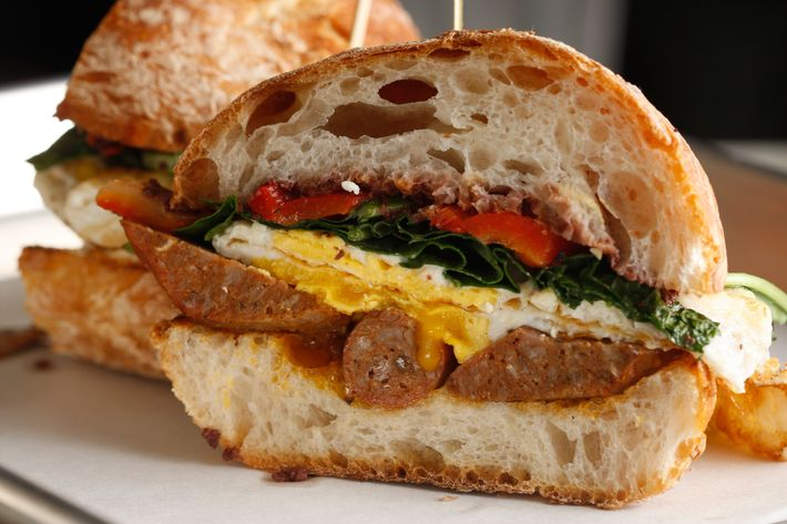 Greeky-Roman: lamb sausage, feta, roasted peppers, baby kale, olive tapenade, Pugliese roll.
