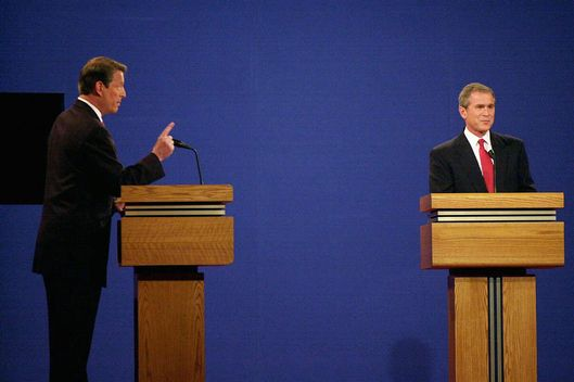 Republican presidential candidate George W. Bush (R) listens to his Democratic opponent Al Gore during their debate 03 October, 2000, at the University of Massachusetts-Boston. This is the first of three debates scheduled between the candidates, leading to the 07 November election.