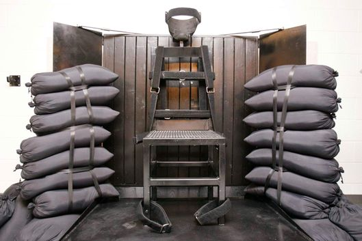 18 Jun 2010, Utah, USA --- The execution chamber at the Utah State Prison is seen after Ronnie Lee Gardner was executed by a firing squad in Draper June 18, 2010. Four bullet holes are visible in the wood panel behind the chair. Gardner, 49, was pronounced dead at 12:20 a.m. Mountain Time (0620 GMT) after being shot in the chest by a five-man firing squad at the Utah State Prison in Draper, a suburb of Salt Lake City. Gardner was condemned to die for the 1985 courthouse shooting of attorney Michael Burdell during an escape attempt. Gardner had been in court to face a charge of murdering a bartender. REUTERS/Trent Nelson-Salt Lake Tribune/Pool (UNITED STATES - Tags: CRIME LAW IMAGES OF THE DAY) --- Image by ? POOL/Reuters/Corbis