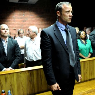 South African Olympic sprinter Oscar Pistorius (C) appears on February 19, 2013 at the Magistrate Court in Pretoria as he father Henke (3rd L), brother Carl (2nd L) and sister Aimee (L) attend. Pistorius battled to secure bail as he appeared on charges of murdering his model girlfriend Reeva Steenkamp on February 14, Valentine's Day. South African prosecutors will argue that Pistorius is guilty of premeditated murder in Steenkamp's death, a charge which could carry a life sentence.