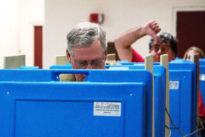A voter gestures as Senate Minority Leader U.S. Sen. Mitch McConnell (R-KY) votes in the midterm elections at Bellarmine University November 4, 2014 in Louisville, Kentucky. McConnell is running in a tight race against opponent Kentucky Secretary of State Alison Lundergan Grimes.