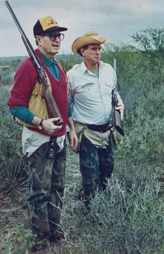 US Pres. George Bush dressed in hunting gear w. friend/oil heir William Farish, both sporting rifles, on quail hunt at Lazy F ranch.  (Photo by David Valdez/White House/Time Life Pictures/Getty Images)