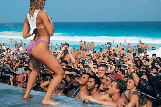 A young American woman dances before the students during a wet t-shirt contest Thursday March 20, 2003, in Cancun, Mexico. Every year, tens of thousands of American spring breakers descend on Cancun, where the sun is hot the beaches are powder-white and the drinking age is all-but nonexistent.(AP Photo/Jose Luis Magana)