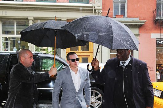 Casper Smart spotted being helped by two guys with umbrellas on a rainy day in New York City.