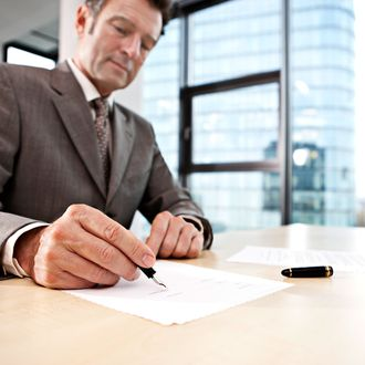 Businessman signing document at desk