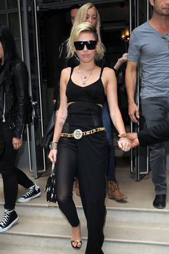Singer Miley Cyrus dressed in high waist black sheer trousers with a buttoned drape leg and a fitted black bra top, seen leaving a London hotel.