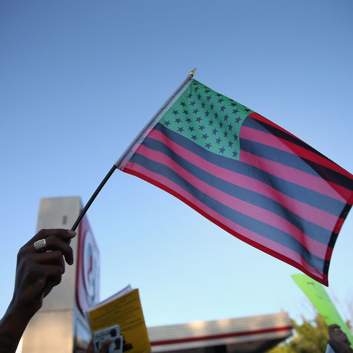 FERGUSON, MO - AUGUST 12: Demonstrators hold up an African American Flag during a protest the killing of teenager Michael Brown on August 12, 2014 in Ferguson, Missouri. Brown was shot and killed by a police officer on Saturday in the St. Louis suburb of Ferguson. Ferguson has experienced two days of violent protests since the killing but, tonight's protest was peaceful. (Photo by Scott Olson/Getty Images)