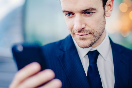 Businessman texting on smartphone in front of office