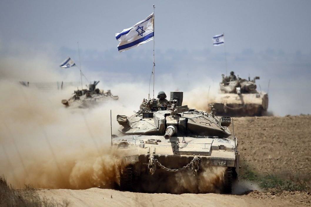 Israeli Merkava tanks roll near the border between Israel and the Gaza Strip as they return from the Hamas-controlled Palestinian coastal enclave on August 5, 2014, after Israel announced that all of its troops had withdrawn from Gaza. Israel completed the withdrawal of all troops from Gaza as a 72-hour humanitarian truce went into effect following intense global pressure to end the bloody conflict. AFP PHOTO / THOMAS COEX        (Photo credit should read THOMAS COEX/AFP/Getty Images)
