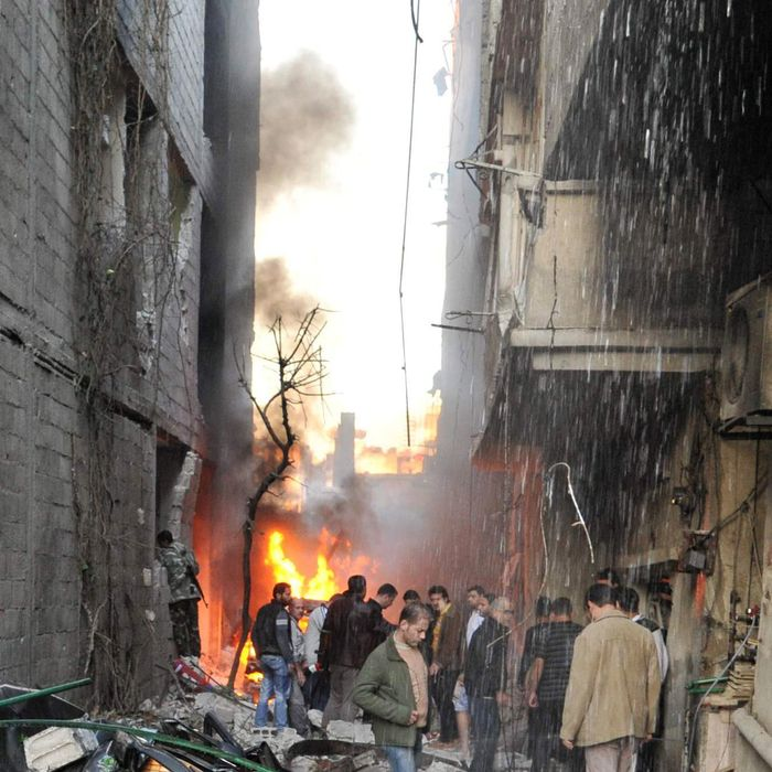 Syrian men inspect the scene of a car bomb explosion in Jaramana, a mainly Christian and Druze suburb of Damascus, on November 28, 2012. At least two car bombs exploded in Damascus killing and injureing a numbe of people.