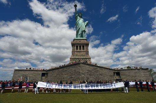Children with flags stand in front of the Statue of Liberty on June 6, 2014 on Liberty Island in New York. Thousands gathered on the island to participate in ceremonies commemorating the 70th anniversary of D-Day