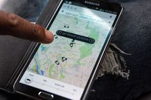 UberX driver checks the Uber customer app to see where other Uber drivers are working so he can determine where the best place for him to get fares might be, April 7, 2014, in Washington, DC.