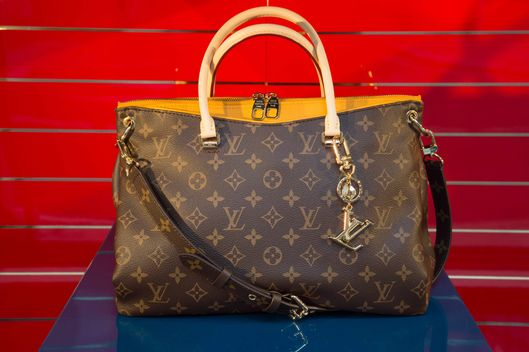 Bag in the shop window of Louis Vuitton store in the City of London, UK. Louis Vuitton Malletier, commonly referred to as Louis Vuitton or shortened to LV, is a French fashion house founded in 1854 by Louis Vuitton. The label's LV monogram appears on most of its products, ranging from luxury trunks and leather goods to ready-to-wear, shoes, watches, jewelry, accessories, sunglasses, and books.