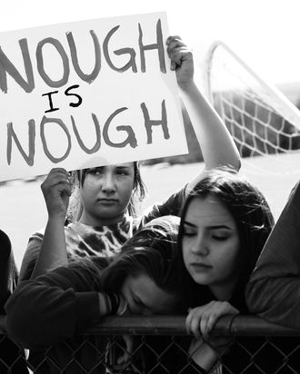 A student a Columbine High School holds up a sign that reads,