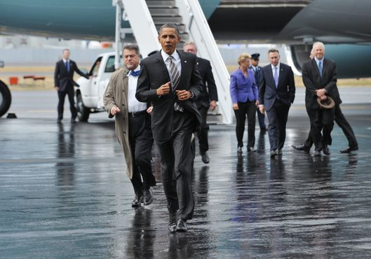US President Barack Obama jogs over to greets well-wishers upon arrival at King County International Airport in Seattle on September 25, 2011. Obama is in Seattle to attend campaign fundraisers.