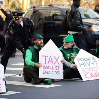 NEW YORK, NY - DECEMBER 01: AIDS protesters sit down in the street after marching up Broadway from Zuccotti Park on World AIDS Day on December 1, 2011 in New York City. About a half-dozen protesters, part of a larger group of over 100, were arrested after refusing to move while calling for Mayor Michael Bloomberg and members of Congress to tax Wall Street trade to raise money for AIDS treatment. (Photo by Spencer Platt/Getty Images)