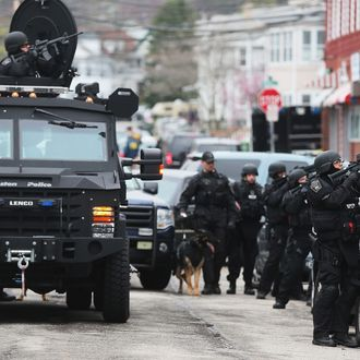 WATERTOWN, MA - APRIL 19: SWAT team members aim their guns as they search for one remaining suspect at an apartment building on April 19, 2013 in Watertown, Massachusetts. Earlier, a Massachusetts Institute of Technology campus police officer was shot and killed at the school's campus in Cambridge. A short time later, police reported exchanging gunfire with alleged carjackers in Watertown, a city near Cambridge. According to reports, one suspect has been killed during a car chase and the police are seeking another - believed to be the same person (known as Suspect Two) wanted in connection with the deadly bombing at the Boston Marathon earlier this week. Police have confirmed that the dead assailant is Suspect One from the recently released marathon bombing photographs. (Photo by Mario Tama/Getty Images)
