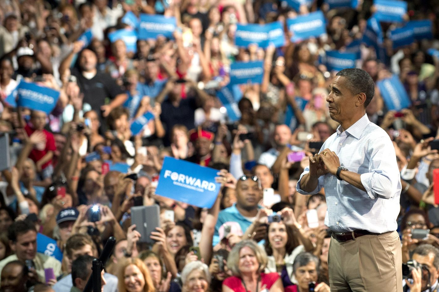 US President Barack Obama makes a heart with his hands as he arrives to speak during a campaign event at the Palm Beach County Convention Center in West Palm Beach, Florida, on September 9, 2012 during the second day of a 2-day bus tour across Florida.