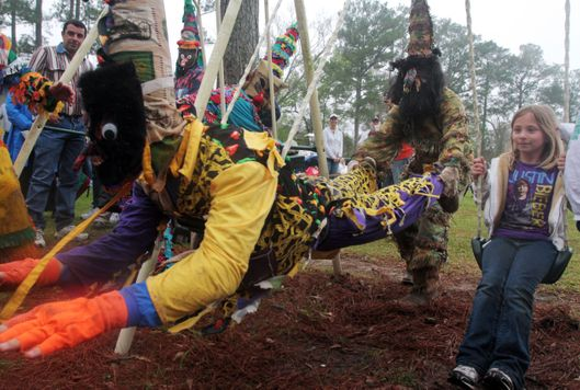 Rylie Durio, 7, plays on a swingset alongside costumed courir participants, known as Mardi Gras, during the Tee Mamou-Iota Courir de Mardi Gras near Iota, La., Tuesday, March 8, 2011. (AP Photo/The Daily Advertiser, Leslie Westbrook)