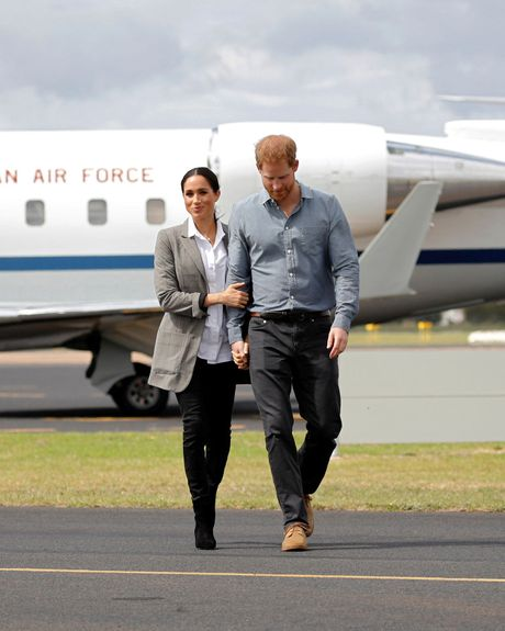 Meghan Markle and Prince Harry hold hands.