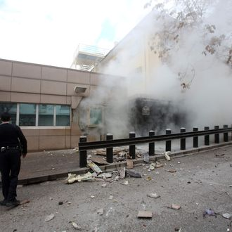People stand outside the entrance of the US Embassy in Ankara just after a blast killed two security guards and wounded several other people on February 1, 2013. The United States confirmed on February 1 that its embassy in Ankara had been hit by a 'terrorist' bomb attack and said American officials were working with Turkish investigators. 'We can confirm a terrorist blast at a check point on the perimeter of our embassy compound in Ankara, Turkey, at 1:13 p.m. local time,' State Department spokeswoman Victoria Nuland said in a statement.