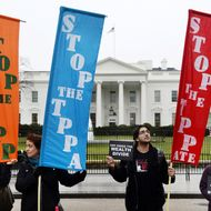 Activists hold a rally to protest the Trans-Pacific Partnership (TPP) in front of the White house on February 3, 2016 in Washington, DC. The TPP trade pact is expected to be signed in New Zealand on February 4.