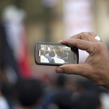 """A man uses his a cellphone to record the activity of fellow pro-reform protestors during a massive demonstration in Cairo's Tahrir square on November 24, 2011. Members of Egypt's ruling military council rejected calls to step down immediately, saying it would amount to a """"betrayal"""" as anti-military protests entered their seventh day. AFP PHOTO/ODD ANDERSEN (Photo credit should read ODD ANDERSEN/AFP/Getty Images)"""