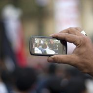 A man uses his a cellphone to record the activity of fellow pro-reform protestors during a massive demonstration in Cairo's Tahrir square on November 24, 2011. Members of Egypt's ruling military council rejected calls to step down immediately, saying it would amount to a